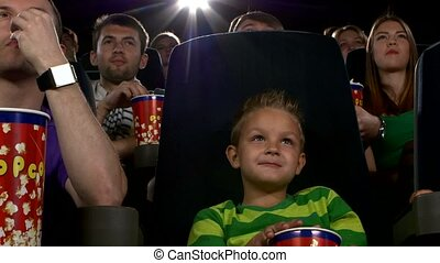 Little boy eating popcorn and watching movie at the cinema -...