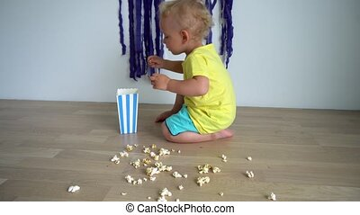Little boy eating popcorns and doing mess on floor at home. ...