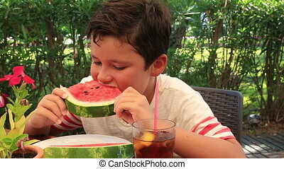 Little boy eating watermelon at the restaurant