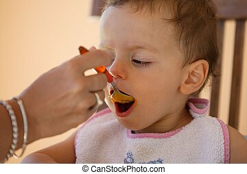 little boy eating with a spoon