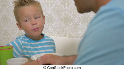 Little boy eating with his dad, they talk about something