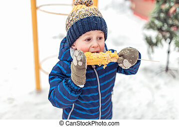 little boy eats boiled corn in winter at fair, on weekends in nature, a blue warm jumpsuit, a warm hat, a snack for breakfast and lunch in nature in winter. Vacation concept resort with a child.