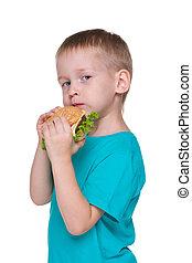 Little boy eats hamburger
