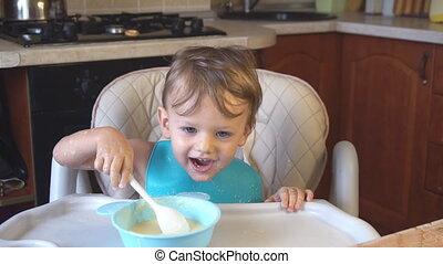 little boy eats porridge for breakfast