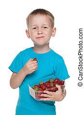 Little boy eats strawberry