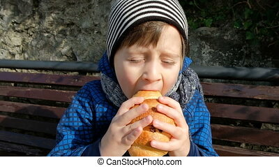 Little boy enjoy eating large croissant sitting on bench outdoor.