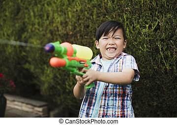 Little boy Enjoying a Garden Water Fight