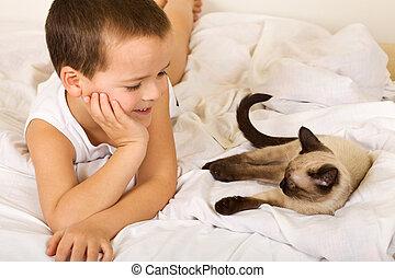 Little boy enjoying the company of his kitten
