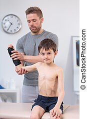 Little boy exercising with physiotherapist