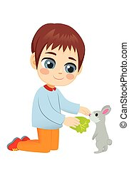 Little Boy Feeding Pet Rabbit - Young little boy feeding...