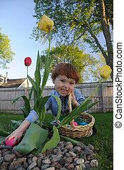Little boy finds an egg during an Easter egg hunt