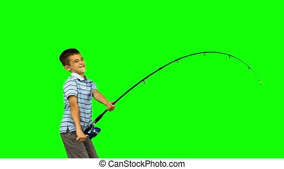 Little boy fishing on green screen in slow motion