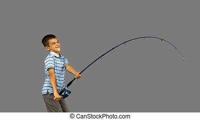 Little boy fishing on grey screen in slow motion