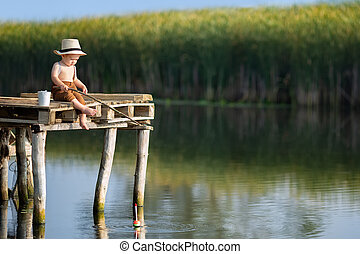 little boy fishing on the lake - little boy sitting on ...