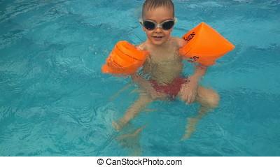 Little boy floating in swimming pool, slow motion