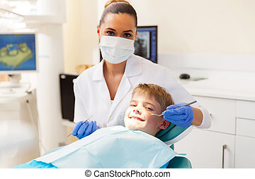 little boy getting dental checkup in dentist office