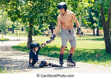 Little boy getting help from his grandpa after rolleskating fall
