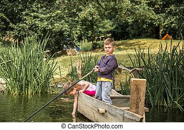 Little boy girl fishing in a boat