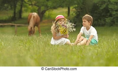 Little boy gives a bouquet of wild flowers to a girl. Slow motion