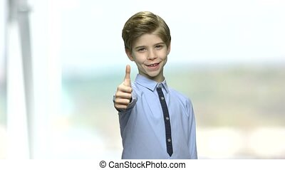 Little boy giving thumb up sign. Stylish preteen boy...