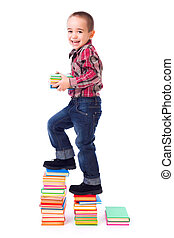 Little boy going up stairs made of books
