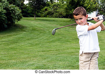 Little boy golfer swinging a club on the golf course