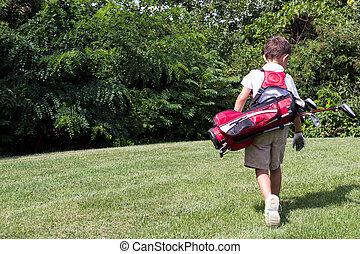 Little boy golfer walking with his golf bag on the fairway