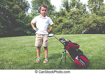 Little boy golfer with his golf bag on the fairway