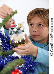 Little boy hanging decorations on Christmas tree