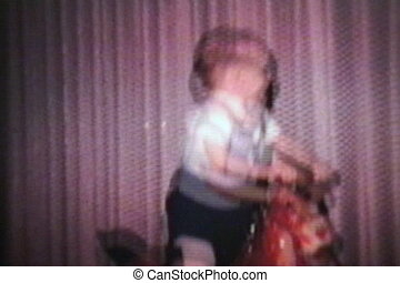 A cute little boy rides his horsey at top speed in the family living room. (Scan from archival 8mm film)