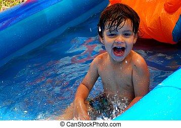 Little boy happy to be in a little pool