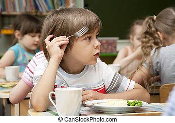 Little boy has a lunch in the kindergarten