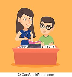 Little boy having a piano lesson with a teacher.
