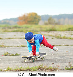 little boy having fun with skateboard outdoors.