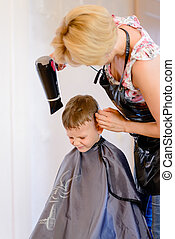 Little boy having his hair blow dried