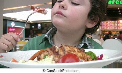 Little boy having lunch at a restaurant