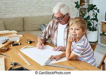 Little Boy Helping Grandpa Make Birdhouse