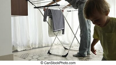 Little boy helping hang laundry his mother at home