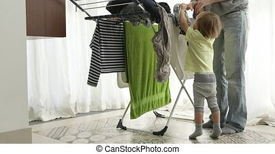 Little boy helping hang laundry his mother