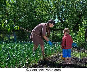 Little boy helping his mother in the garden