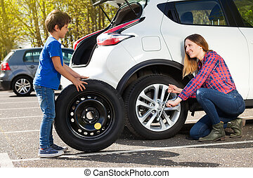 Little boy helping his mother to change flat tyre - Portrait...