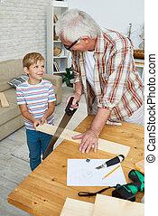 Little Boy Helping Senior Carpenter