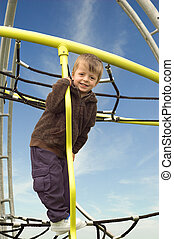 Little boy high up on a climbing frame in the park.