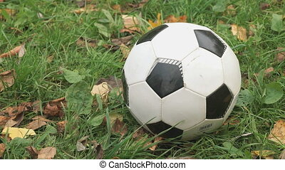 Little boy hits his foot on a soccer ball outdoors