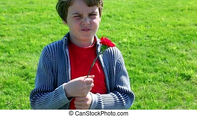 Little boy hold red flower at background of green grass