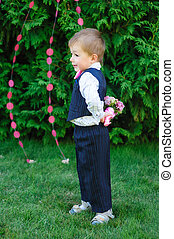 little boy holding a bouquet of flowers in the park