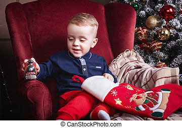 little boy holding a christmas stocking and toy train