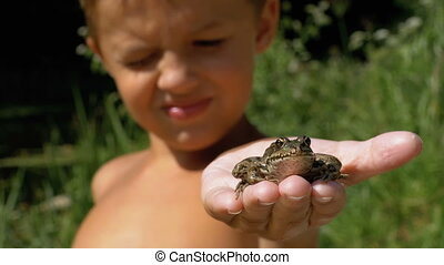 Little Boy Holding a Frog in his Hands on the Beach near the River.