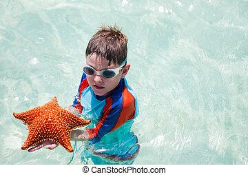 Little boy holding a giant starfish