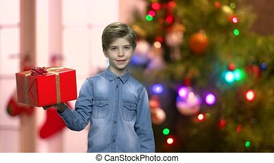 Little boy holding Christmas gift box. Cute child pointing...